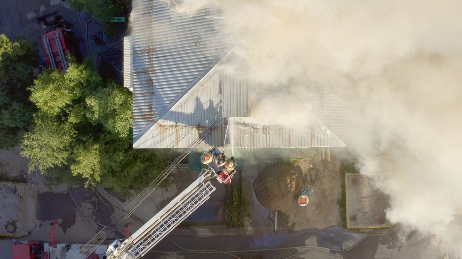 Burning roof of a residential high-rise building, clouds of smoke from the fire. firefighters extinguish the fire. top view